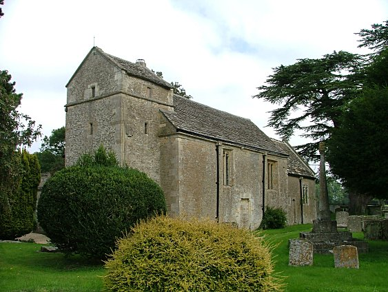 The church with remains of preaching cross on the right. The yawning figure can be see just under the eaves above the blocked doorway.