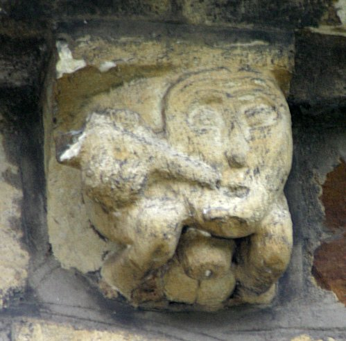 Male Drinker exhibitionist corbel. The testicles and penis with flattened head are clearly visible. This style of execution of the penis can be seen on other Romanesque churches notable examples being in Spain. A small photo of a figure with a similar penis can be found here about half way down the page.