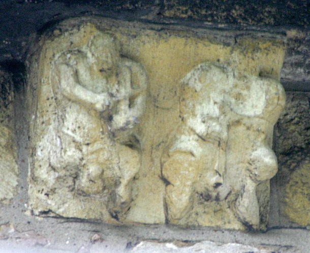 Pair of male musicians (corbel). This corbel seems to be a pair of musicians one playing the fiddle or similar instrument while the other worn figure appears to be playing a pipe. A penis and testicles are clearly visible on the left hand figure while the right hand figure also seems to have a more worn set as well.