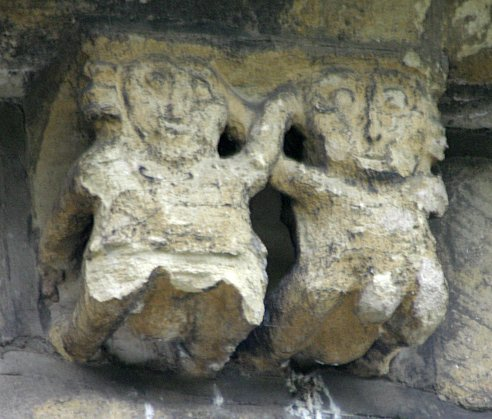 Head holding pair. Both figures seem to have carving in the groin area but it is difficult to say now what they originally represented. Both figures seem to be male but this is questionable. Note that the head on the right hand figure is larger than that on the left. This hand to head gesture is also seen on the Kirknewton figures in Scotland.