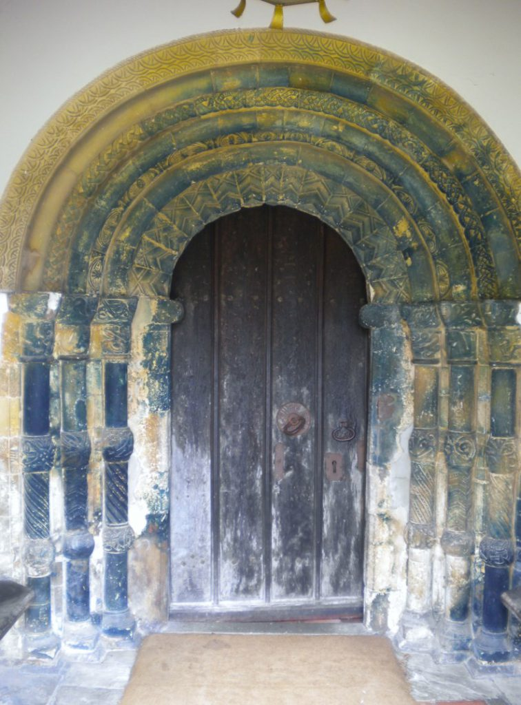The main door to the church with twin figures either side.